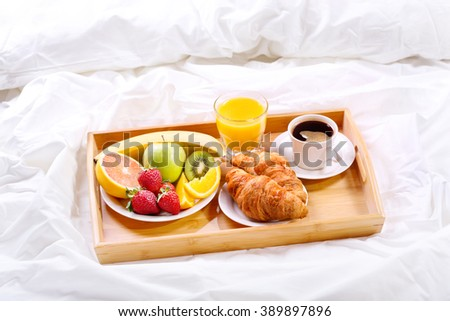 Breakfast in bed. Tray with cup of coffee, juice, croissants and fruits - stock photo