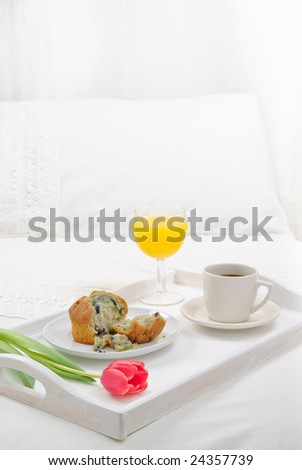 Breakfast in bed with muffin, orange juice and coffee - high key - stock photo