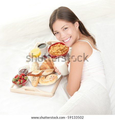 Breakfast in bed. Young woman eating breakfast in bed drinking milk. Beautiful young woman smiling. - stock photo