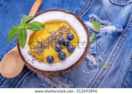Breakfast mango and berry smoothies garnished with chia seeds and bee pollen in coconut on jeans background. Concept of healthy food. selective Focus - stock photo