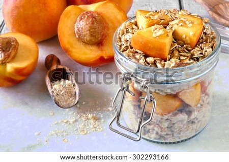 Breakfast oats with fresh peaches and granola in snap lid glass jar on white marble - stock photo