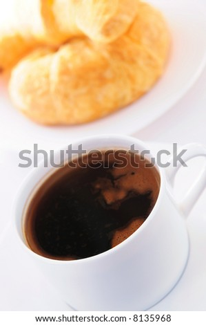 Breakfast of black coffee and fresh croissants