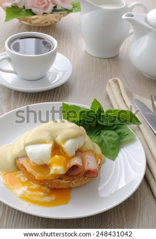 Breakfast of boiled eggs (poached) with ham on a bun with mustard sauce - stock photo