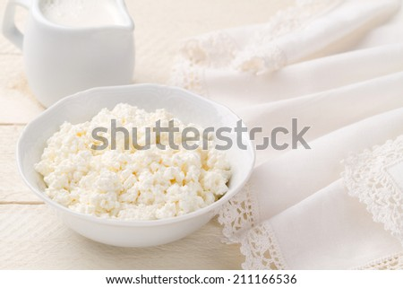 Breakfast of cottage cheese and diary cream on a white wooden table (closeup) - stock photo