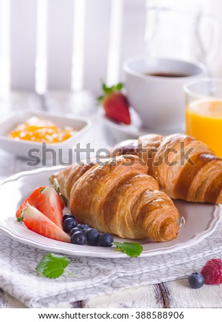 Breakfast of freshly baked croissants with berries and coffee