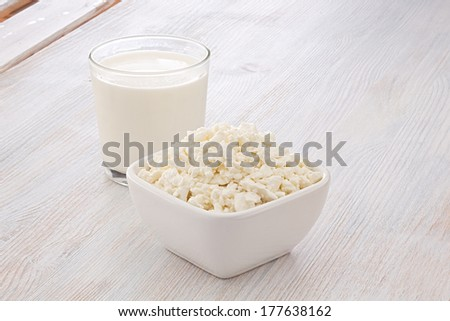 Breakfast of milk and cottage cheese on wooden table - stock photo