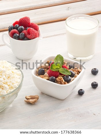Breakfast of muesli with milk, berries and peppermint - stock photo