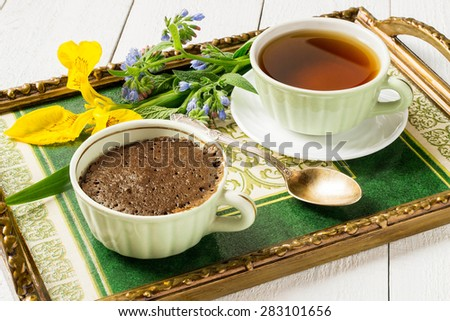 Breakfast on a tray: freshly made chocolate cake, a cup of tea and a bouquet of flowers for a good mood. Selective focus - stock photo