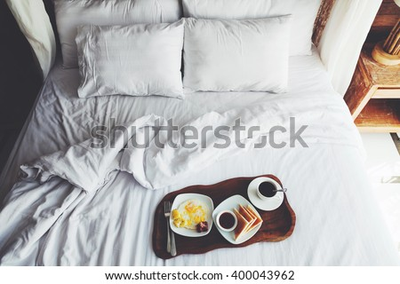 Breakfast on a tray in bed in hotel, white linen, wooden interior - stock photo