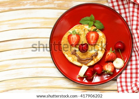 breakfast pancakes with berries (strawberry, cherry, banana), funny face - stock photo
