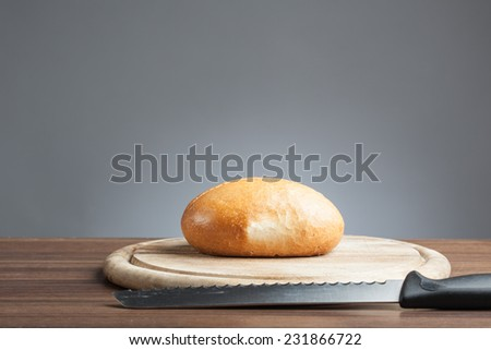 Breakfast plate with cutting knife and a bread roll. - stock photo