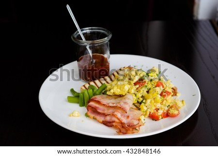 Breakfast plate with scrambled eggs, bacon and toast on a white plate - stock photo
