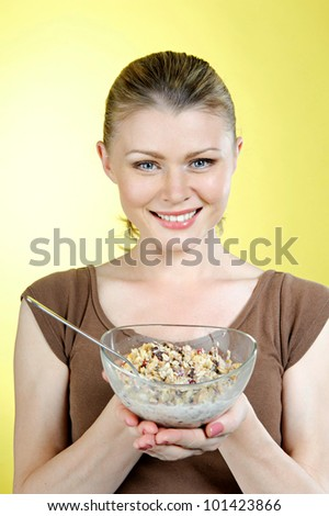Breakfast. Portrait of the beautiful woman with a plate of flakes.