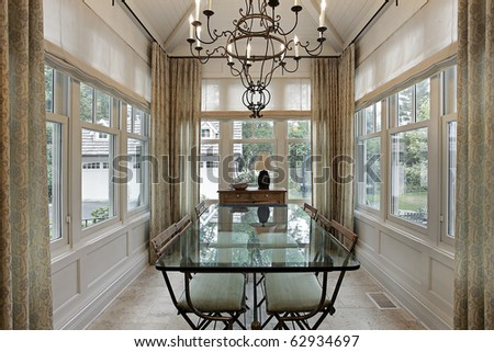 Breakfast room in luxury home surrounded by windows - stock photo