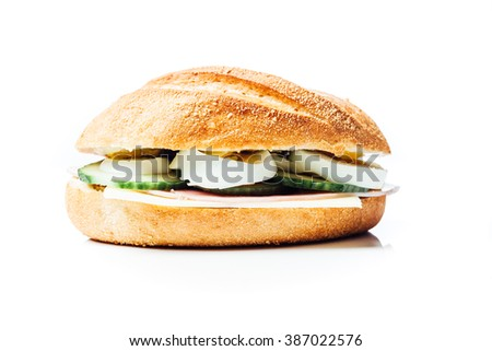 Breakfast sandwich, potato bread roll with cucumber, ham and egg, chees, on white background with reflection.