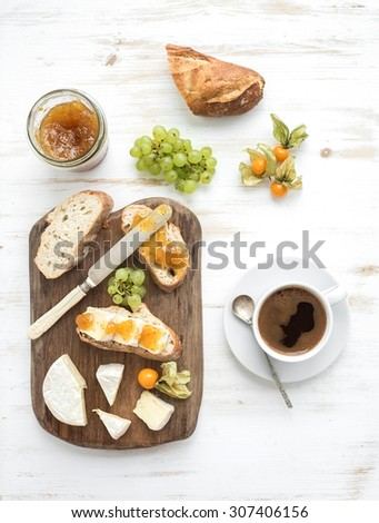 Breakfast set. Brie cheese and fig jam sandwiches with fresh grapes, ground cherries. Cup of coffee. Top view, copy space - stock photo