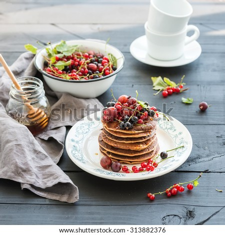 Breakfast set. Buckwheat pancakes with fresh berries and honey on rustic plate over black wooden table - stock photo