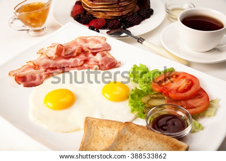 Breakfast set: fried eggs with bacon, pancakes with syrup and berries and tea