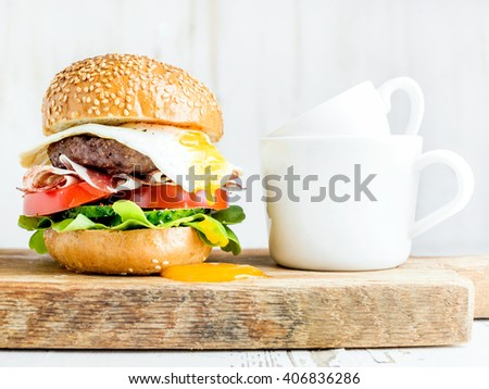 Breakfast set. Homemade beef burger with fried egg and vegetables, onion rings and coffee cups on wooden board, white painted background. Selective focus - stock photo