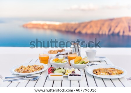 Breakfast table romantic by the sea. Perfect luxury breakfast table for two outdoors. Amazing caldera view on Santorini, Greece, Europe. - stock photo