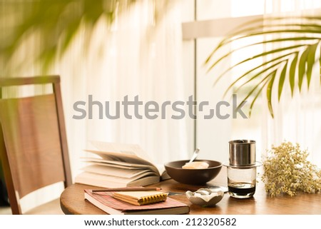 Breakfast table: tea, dish and books - stock photo