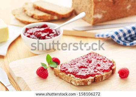 Breakfast table with bread and raspberry jam - stock photo