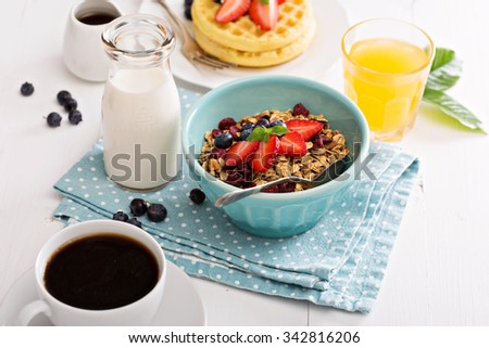 Breakfast table with granola and fresh berries - stock photo
