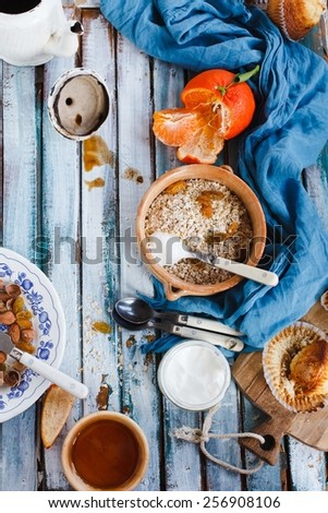 Breakfast table with whole oat flakes, nuts, honey and natural yogurt on a vintage blue wooden table. Concept image for healthy or vegetarian cooking.Natural fruit of garden Rustic style  - stock photo