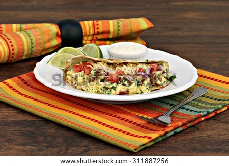 Breakfast taco with scrambled eggs, shredded cheese, chorizo, peppers and onions with a side of lime slices and sour cream.  Selective focus on front of taco. - stock photo