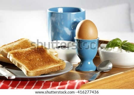 breakfast time in bed and blue mug and egg and bread  - stock photo