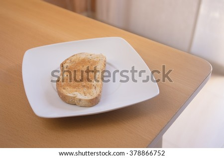 Breakfast. Toasted bread on a white plate with natural light on a table.  - stock photo