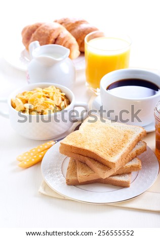 Breakfast: toasts, marmalade, cup of coffee, orange juice, cornflakes - stock photo