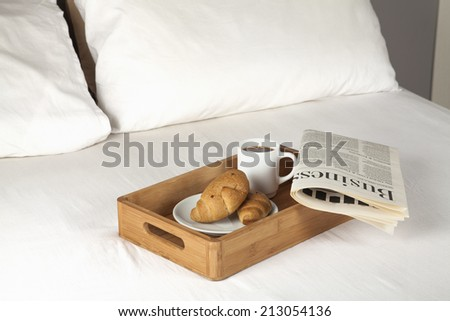 Breakfast tray and newspaper on a bed - stock photo