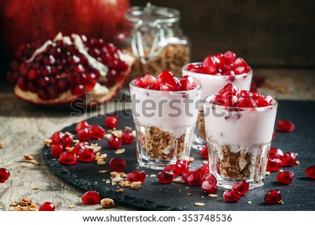 Breakfast with baked muesli, yoghurt and pomegranate, portioned in glasses on a dark background, selective focus - stock photo