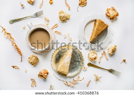 Breakfast with cake, beige rose flower, petals, vintage plates, retro fork and cup of coffee with milk composition. Flat lay, top view - stock photo