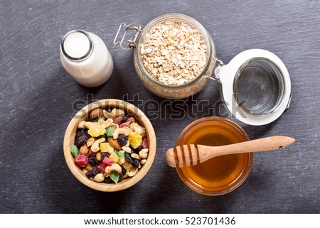 breakfast with cereal, dried fruits, milk and honey on dark background, top view with copy space.