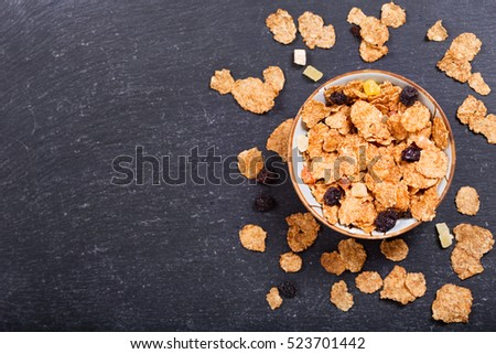 breakfast with cereal flakes on dark background, top view with copy space.