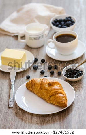 Breakfast with croissant,  milk, butter, huckleberry jam and coffee