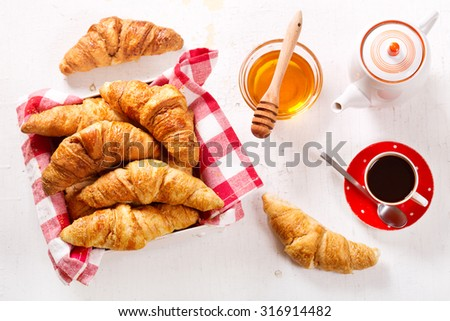 breakfast with croissants and coffee on wooden table
