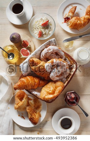 Breakfast with croissants,  figs, curd, honey and espresso coffee on rustic serving board o, top view, vertical composition