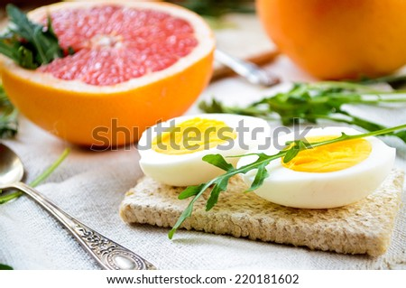 breakfast with eggs, grapefruit and fresh rucola - stock photo