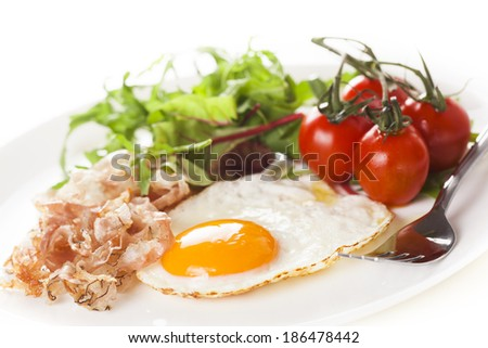 Breakfast with eggs, ham and fresh salad with tomatoes. - stock photo