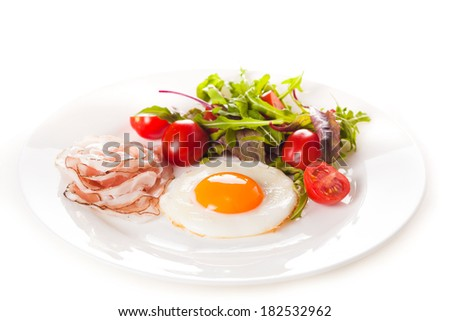 Breakfast with eggs, ham and fresh salad with tomatoes isolated