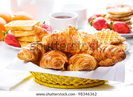 breakfast with fresh croissants, berries and fruits - stock photo