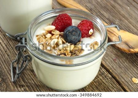 breakfast with fresh yogurt, berries and granola  - stock photo
