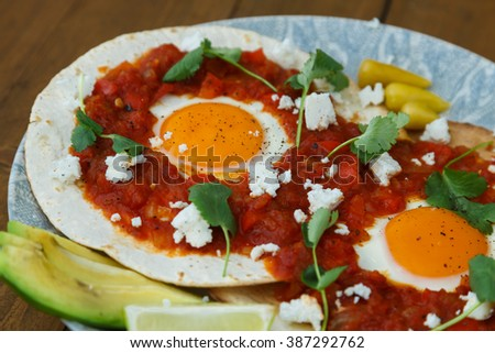 Breakfast with fried egg and sauce on grilled flour tortilla, Mexican dish huevos rancheros. - stock photo