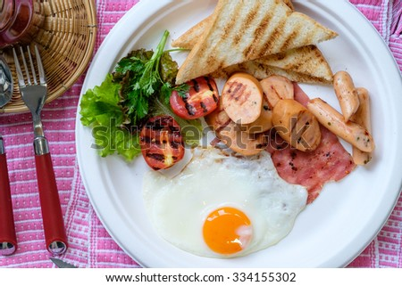 breakfast with fried eggs, bacon, sausages, beans, toasts and fresh salad - stock photo