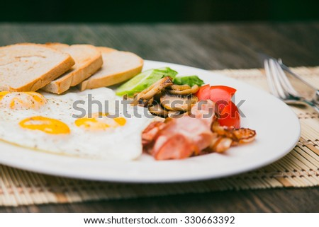 breakfast with fried eggs, bacon, toasts and fresh salad - stock photo