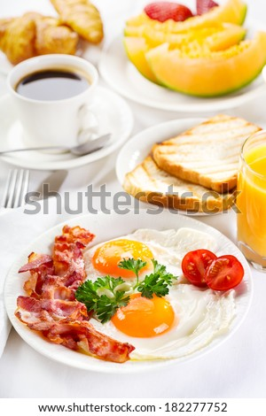 Breakfast with fried eggs, coffee, orange juice, croissant, toasts  and fruits - stock photo