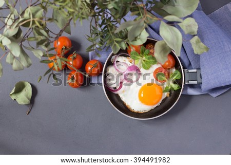 Breakfast with fried eggs served in frying pan with tomatoes, herbs, spinach - stock photo